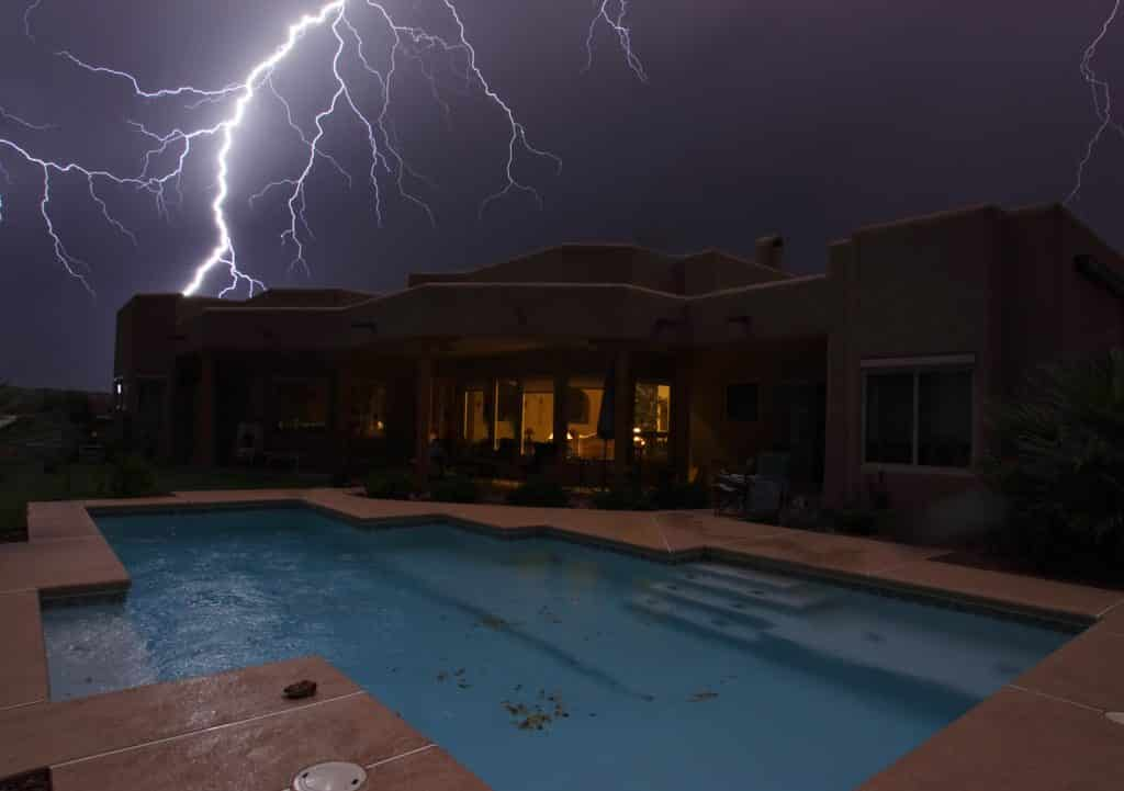 Lightning strikes over a house and swimming pool.
